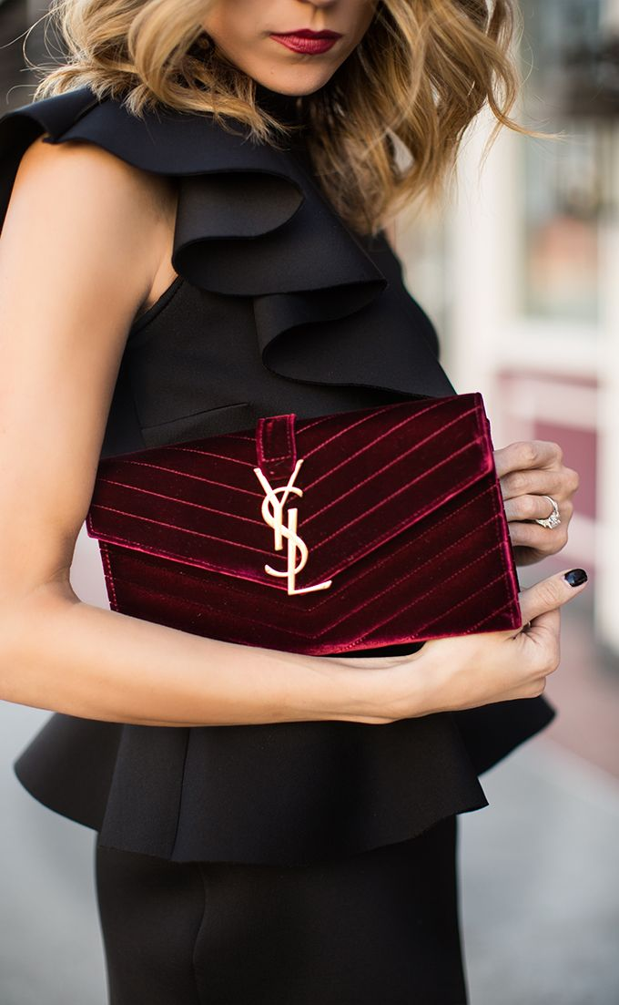 Women's fashion ruffling black top with burgundy Yves Saint-Laurent velvet purse.