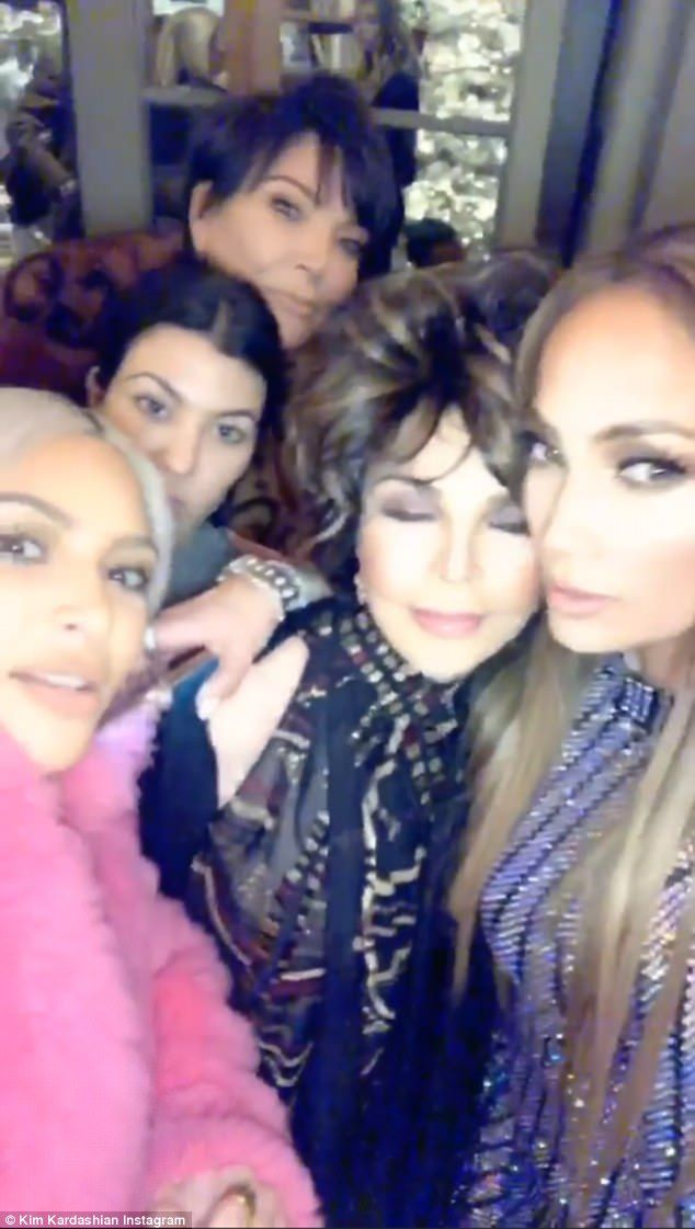 Oops:Kim appeared to have slyly tricked her host along with what appeared to be Joan Collins by revealing they were being video taped rather than photographed for a group shot