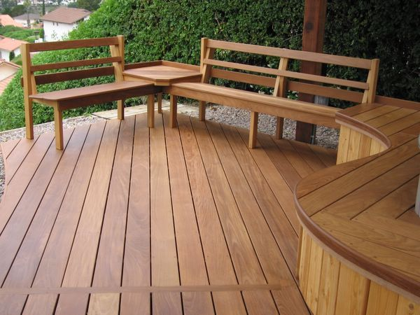 This is a stunning wood deck with a wooden seat wall and benches