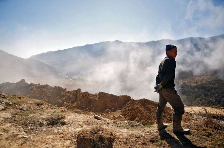 Dance bars, mobile phones and Chelsea jerseys: changing face of Bhutan - January 18, 2018.  Smoke billows from machinery at a road construction site near the town of Punakha, Bhutan.