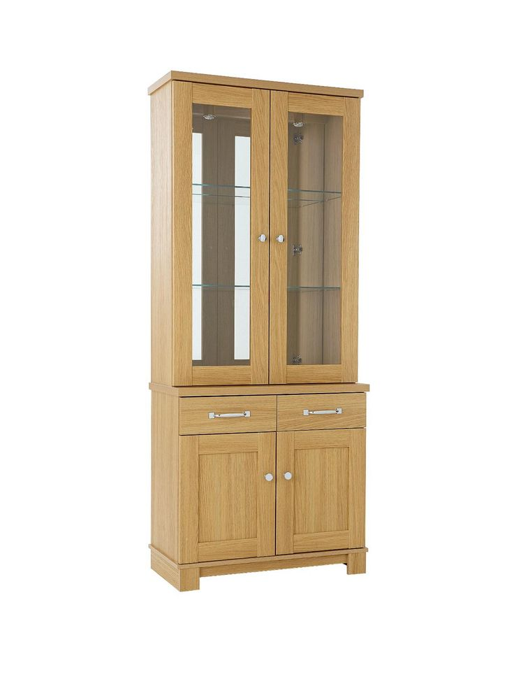 Belvoir Ready Assembled 2-Door Glass Display Unit in Oak-EffectBeautifully textured new oak-effect finish with optical emboss. Cabinets have thick framed doors and small leg plinth detail and thick drawer fronts with oak-effect drawer boxes. Downlights, glass shelves and mirrored backs to display cabinets. Bright chrome handles and knobs compliment the range complete with metal drawer runners for easy glide action and adjustable metal hinges for alignment on uneven floors.H 198, W 82, D 40…