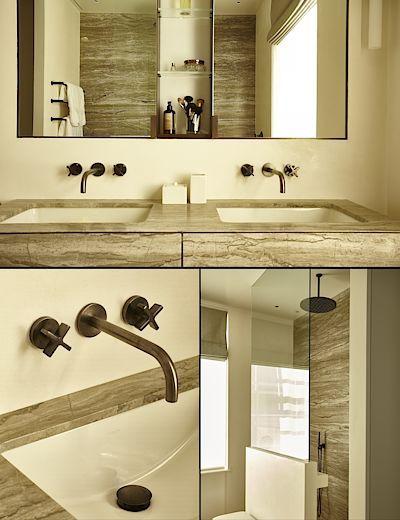 Interiér koupelny rodičů je zařízen leštěnými msaznými prvky a deskami a obklady z travertinu.