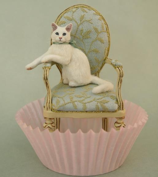 Miniature sculpted cat on a 1/12 scale dollhouse chair.