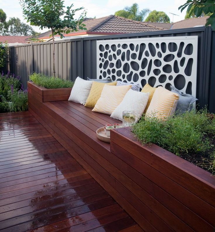 Built in seats, surrounded by garden bed and cut screen on fence.