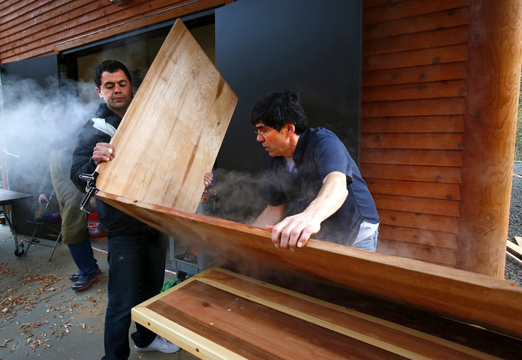 The first class of students at the newly opened carving shed at Evergreen State College learned to make bentwood box drums from master carver David Boxley this past weekend. Clifton Guthrie, at left, puts a bend in his box drum after steaming the cedar board to soften the wood.