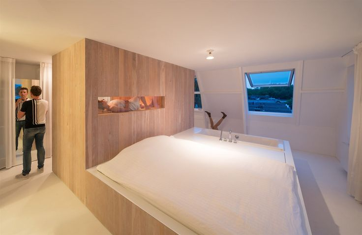 Ve stěně sauny je vyříznutý prosklený izolovaný otvor, takže ležící postava, která si dopřává saunování, se stává součástí kompozice ložnice.