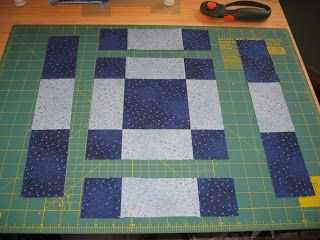 """Disappearing NINE Patch"" Variation, step 1 - from Outside the Line Design blog;  cut through the center of the outside blocks;  then through the center of the now-shorter other outside blocks;  Do this to two blocks, one with five colored squares, one with four colored squares."