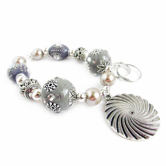 These beaded curtain tiebacks are made with lots of pretty neutral colored beads to match any home decor. A large silver swirl pendant hangs from the center for an added touch. The new year brings new decorating inspiration and these curtain holdbacks have tons of glitz and glam.