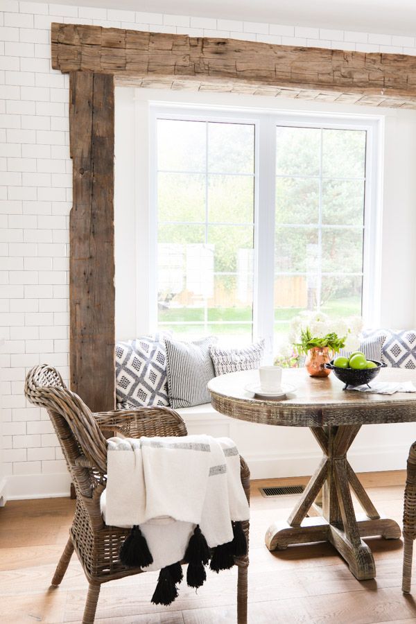 White lake house kitchen featuring a rustic beam breakfast nook area with a window seat, subway tile and blue and white accent pillows.      SAVED BY WENDY SIMMONS