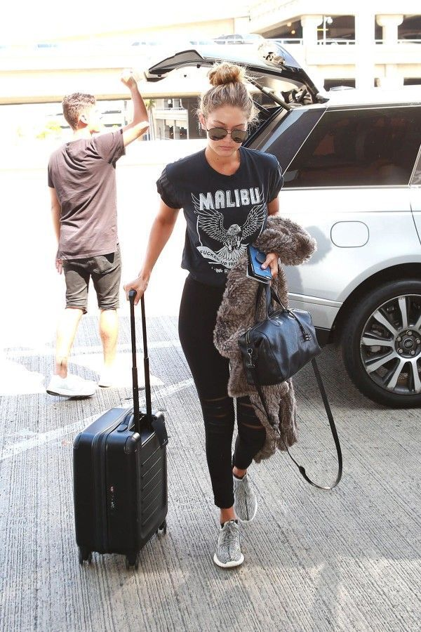 Gigi Hadid's Airport Style | Vintage tee, black skinny jeans and sneakers with a furry coat and aviator sunglasses