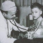 Foto: Dr. C. Walton Lillehei mit einem Kind, das einen der frühen externen Schrittmacher von Medtronic trägt.