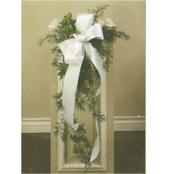 simply live greenery and a large white satin bow for striking and elegant pew markers for any Church ceremony