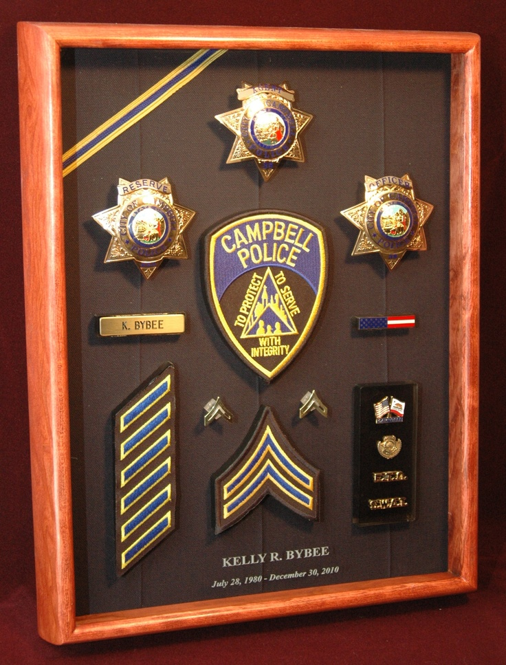This has an unusual backing fabric. Instead of the usual velveteen, the fabric used here was cut from a police uniform shirt. Also, instead of an engraved plate with the officer's name and info, the text was etched into the glass at the bottom of the display. From ShadowBoxUSA.com.