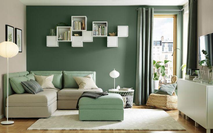 """Ein kleines Wohnzimmer u. a. mit VALLENTUNA 3er-Ecksitzelement/Liege mit den Bezügen """"Orrsta"""" beige und """"Hillared"""" grün und einem weißen Sideboard"""