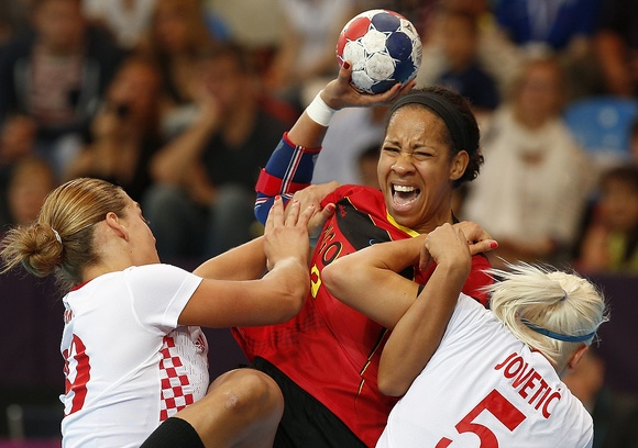 Nair Almeida of Angola, center, is challenged by Croatia's Dijana Jovetic, right, and Sonja Basic, left, during their women's handball preliminary match at the 2012 Summer Olympics, Monday, July 30, 2012, in London. (AP Photo/Vadim Ghirda)