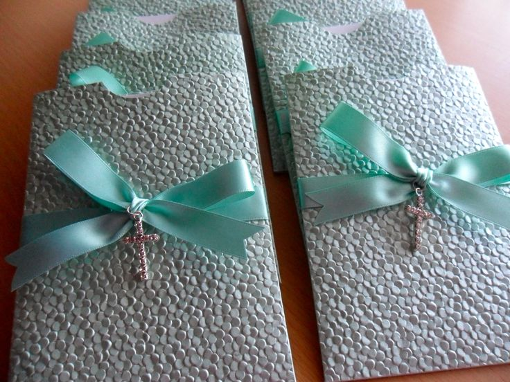 Gorgeous pastel green pebble pocket invitations with aqua ribbon and a diamante cross. Perfect for a Christening/Baptism