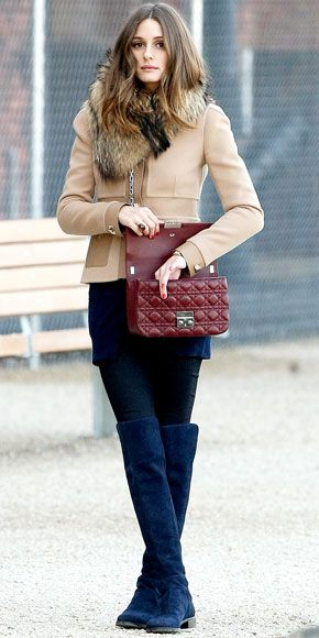 Olivia Palermo in a faux-fur stole, beige jacket, black pants and over-the-knee boots.