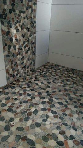 Mooie natuursteen kiezels op vloer en wand te Holten.
