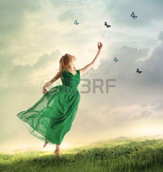 mariposa: Mujer hermosa en un vestido verde cazando mariposas en una montaña Foto de archivo