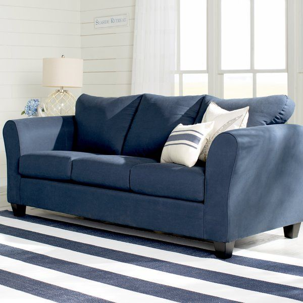 Complete your living room or den seating group in simple style with the understated Fredericktown Sofa, featuring a clean-lined silhouette, navy toned polyester blend upholstery, and a sturdy wood frame. Set it over a neutral chevron rug in green and beige hues, then top it with complementary, patterned throw pillows and comfy cashmere and wool blend throw blankets to tie everything together in luxe style. For a pop of contrast, try setting a bold, coral-hued table lamp on a nearby end…