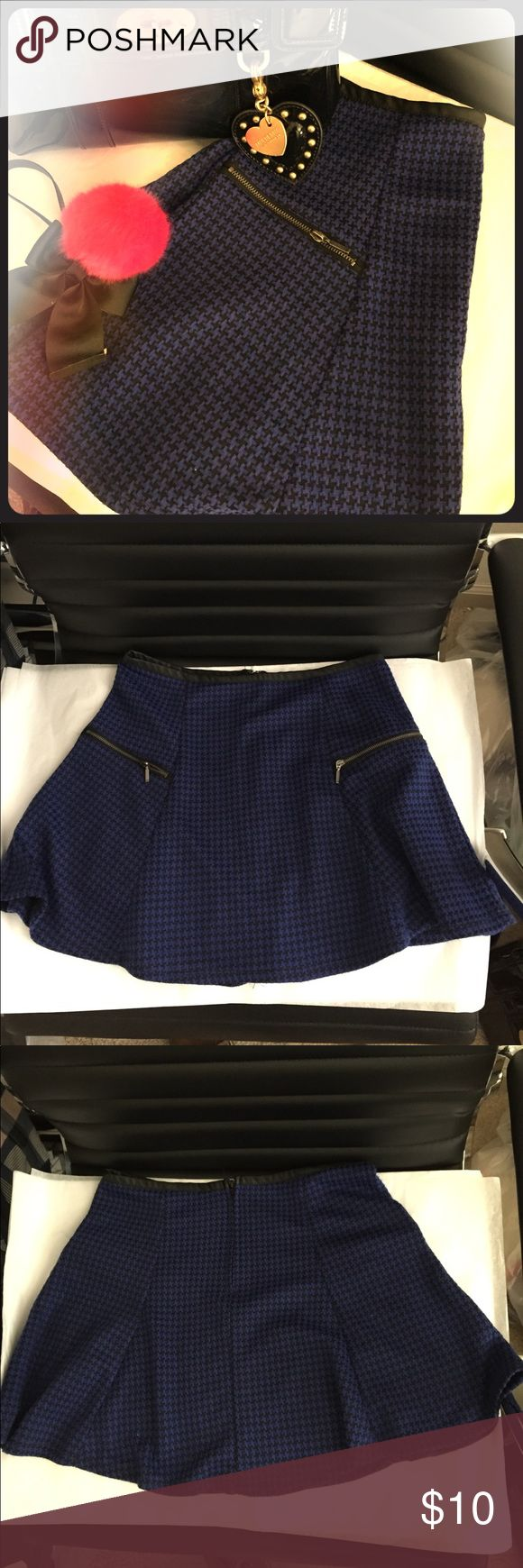 Size L Blue Houndstooth Skirt This is a chic, blue and black houndstooth skirt from Macy's. The brand is Stoosh. It has fake zipper pockets (🙄) but it is still very cute. It also has a zipper on the back. At the top of the waist part, it is trimmed with faux leather. Fabric is perfect for all seasons. Outfit examples could be with a white top and flats for summer, or riding boots and a cowl neck sweater in fall. 😊 Skirt is just above the knees. No rips or stains! Stoosh Skirts