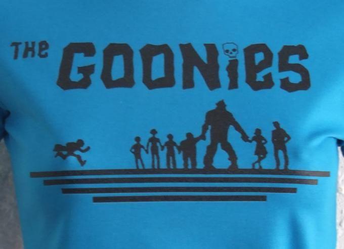 Camiseta chica Los Goonies, azul Pelicula clásica que nos emocionó a muchos de nosotrros en nuestra infancia. En un mundo fantastico y lleno de sueños un grupo de niños luchan para salvar su barrio de unos especuladores inmobiliarios.
