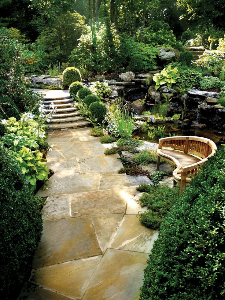 A stone walkway winds through a lush, tranquil Asian-inspired garden featuring a kidney-shaped wooden bench and pond.