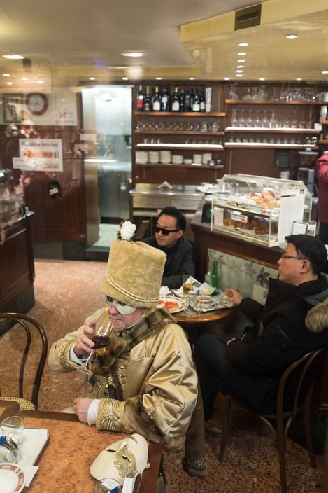 John Vink - Venezia. 28/02/2017: A costumed festival goer relax in a cafe during the carnival celebrations.
