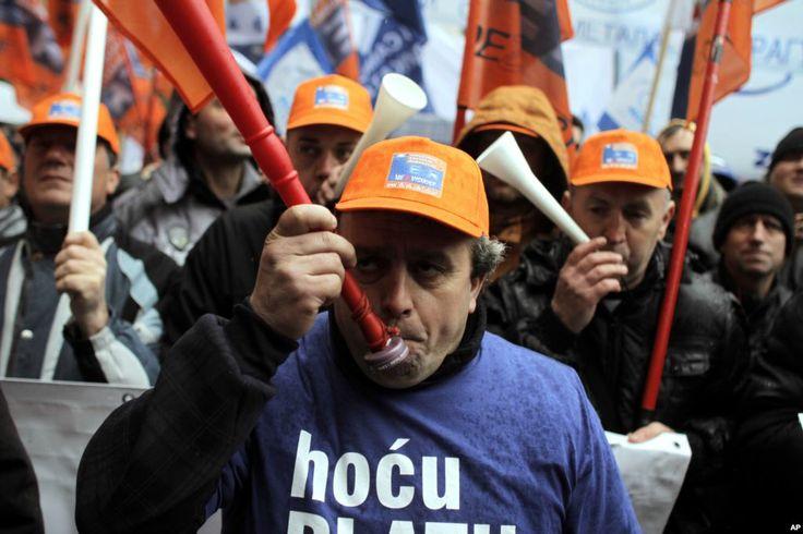 Para anggota serikat pekerja meniup terompet, melakukan protes di Belgrade, Serbia. Sekitar 3.000 pekerja melakukan unjuk rasa menentang serangkaian undang-undang yang menurut pejabat pemerintah adalah penting dalam reformasi anti krisis, tetapi dapat menyebabkan semakin berkurangnya lapangan pekerjaan di negara Balkan yang miskin itu. (26 Januari 2014)