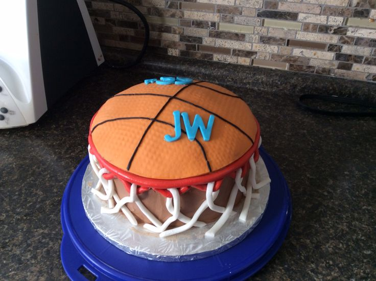 Basketball through a hoop chocolate cake with buttercream icing then covered top with fondant and hoop also out of fondant.