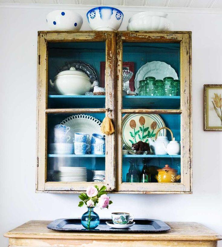 Har du lyckan att komma över ett par gamla fönsterbågar kan du snickra ett charmigt litet vitrinskåp för finsakerna.