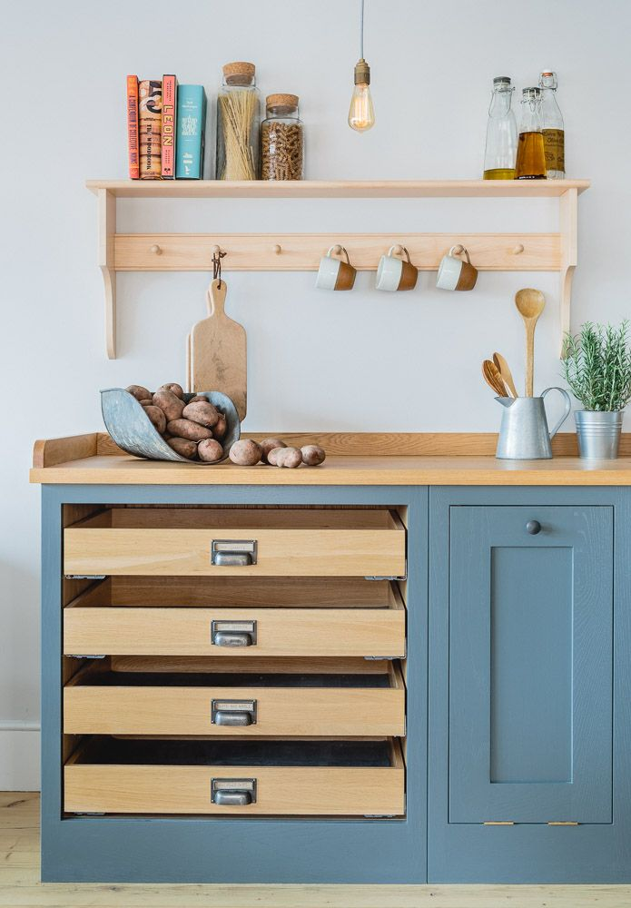 Sustainable Kitchens Showroom. Industrial Shaker Style showroom kitchen with oak cabinetry. The base cabinets are hand painted in Farrow & Ball Down Pipe and have an oak worktop. The shelving is a birch shaker peg shelf and open oak drawers are visible below.
