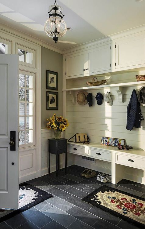 Classy and classic entryway / mudroom. Love the black floor and the white built ins. Pretty rug, too.