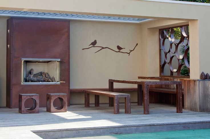 'Winter Branch' laser cut wall deco, outdoor reclaimed timber furniture with metal rivet accents, circular 'bubble' privacy screen and corten rusty fireplace, all custom made by Entanglements matal art