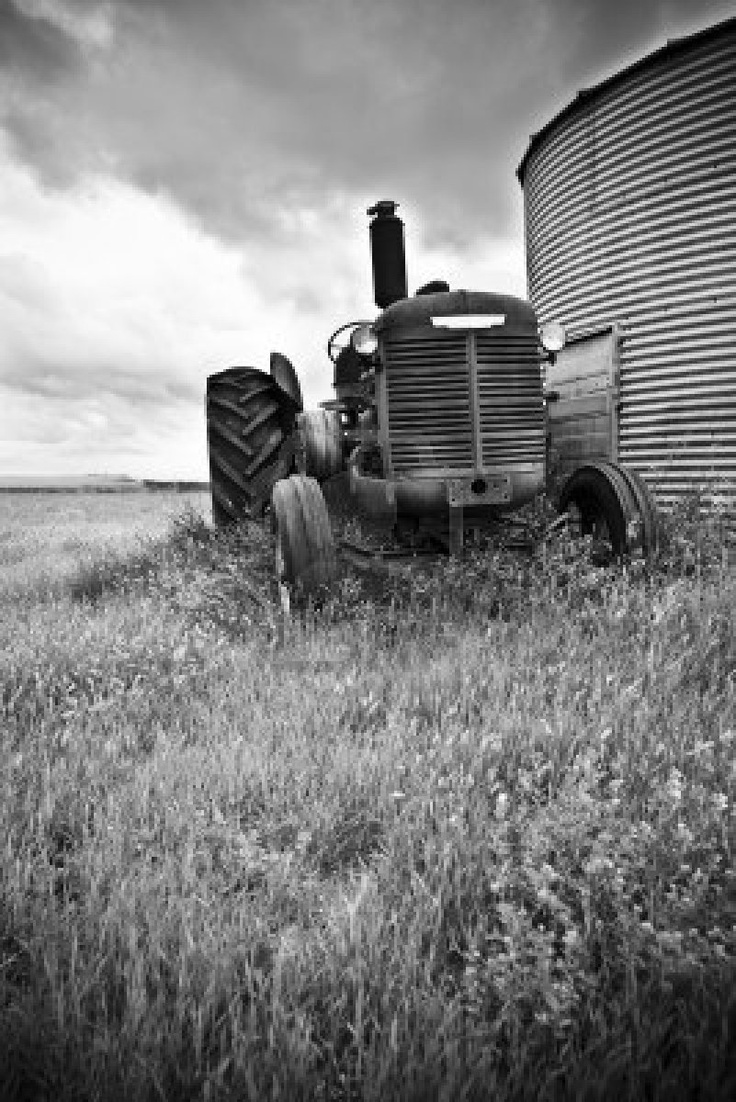 An old tractor standing next to a silo at canadian