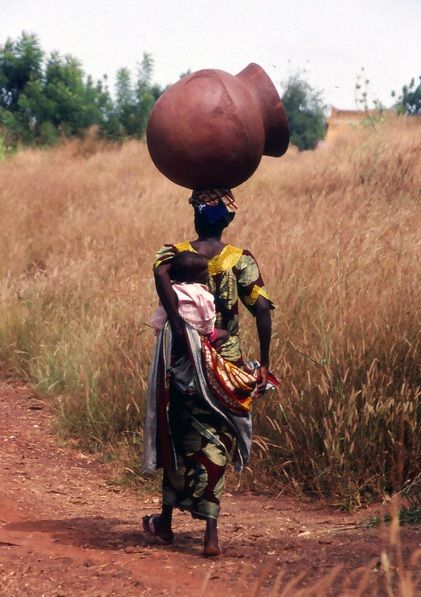 Africa | Woman with a large pot and a baby on her back.  Gaoua. Burkina Faso  | © Michael Sheridan.