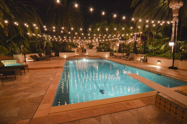 String lights in the backyard over the pool will help with night time ambiance.  I would attach them from the roofline to the fence on the other side of the pool. :)