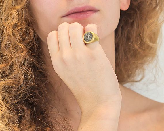 Bring home a piece of ancient Rome with this 18k gold pinky ring with an embedded silver coin. The silver coin goes back to ancient Rome feel like you are a part of history with this one of a kind pinky ring. This ring is preppy, timeless and designed for you. Feel like Roman