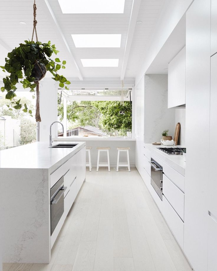 What a pretty kitchen! Super sleek, crisp white cabinets, pops of green from the plants inside and outside, and a super cool bar area at the back too.