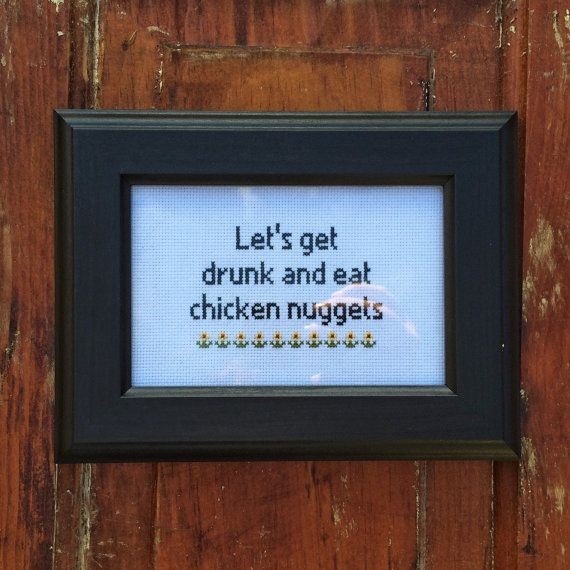 This cross stitch features the phrase lets get drunk and eat chicken nuggets done in black thread with a row of flowers underneath. You have