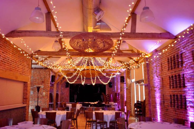 Magenta/pink uplighting with a fairy light star at a Castle Barn Wasing Park wedding