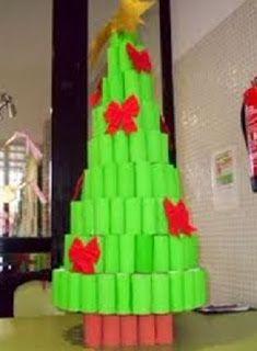 Árbol de navidad hecho con tubos de cartón pintados en color verde. La base es de tubos pintados en color rojo y esta decorado con lazos rojos