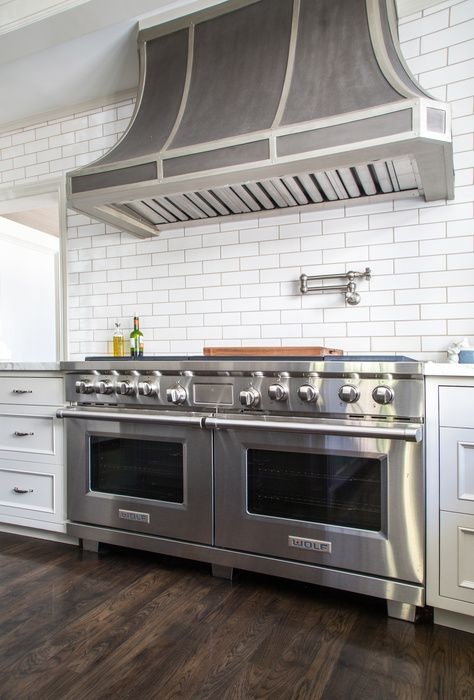 A zinc French range hood stands over a satin nickel swing arm pot filler and a Wolf dual range.