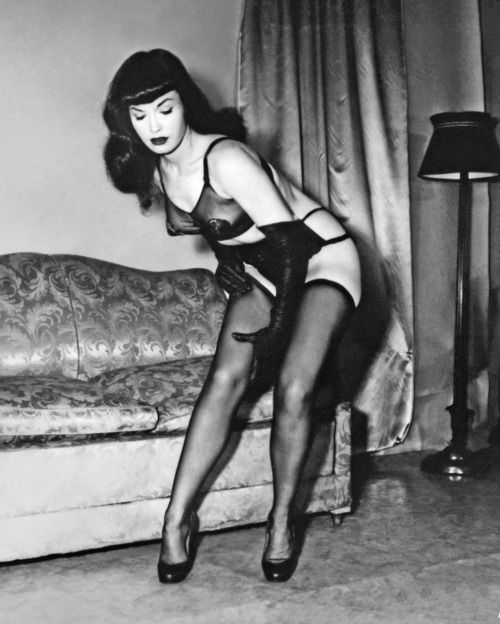 """Bettie Page, circa 1950s, by Irving Klaw. Bettie Mae Page (22 April 1923—11 December 2008) was an American model who became famous in the 1950s for her fetish modeling and pin-up photos. She has often been called the """"Queen of Pinups."""" Her look, including her jet black hair, blue eyes and trademark bangs, has influenced many artists."""