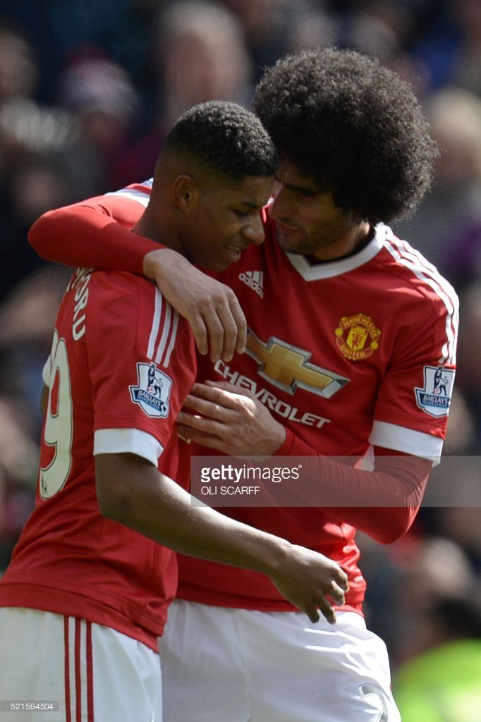 Manchester United's English striker Marcus Rashford (L) embraces Manchester United's Belgian midfielder Marouane Fellaini (R) after scoring the opening goal during the English Premier League football match between Manchester United and Aston Villa at Old Trafford in Manchester, north west England, on April 16, 2016. / AFP / OLI SCARFF / RESTRICTED TO EDITORIAL USE. No use with unauthorized audio, video, data, fixture lists, club/league logos or 'live' services. Online in-match use limited…