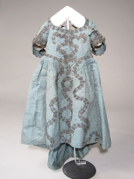 Child's dress, 1760-1770. Light blue figured silk with woven design of latticed ribbons, the ribbons having a spot pattern. Back-fastening, trained skirt and leading strings.