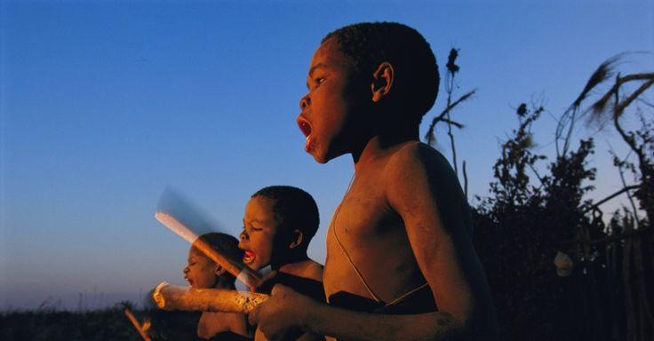 Garotos recém circuncidados da tribo Luvale saúdam o amanhecer com música tradicional e percussão nas margens do rio Zambezi em Lukula, Zâmbia. O rio nasce na Zâmbia e passa por Angola, Namíbia e Zimbábue, onde deságua no Oceano Índico