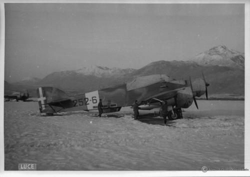 With engines and cockpit covered by canvas against the freezing climate of the Balkan winter, an Italian bomber Savoia-Marchetti S.79 parked on the snow-capped Albanian airfield of Shkodra (Scutari for the Italians).