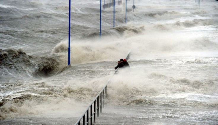 Men hold on to a handrail as waves lash the ferry pier on the North Sea coast in Dagebuell,Germany on December 5, 2013.