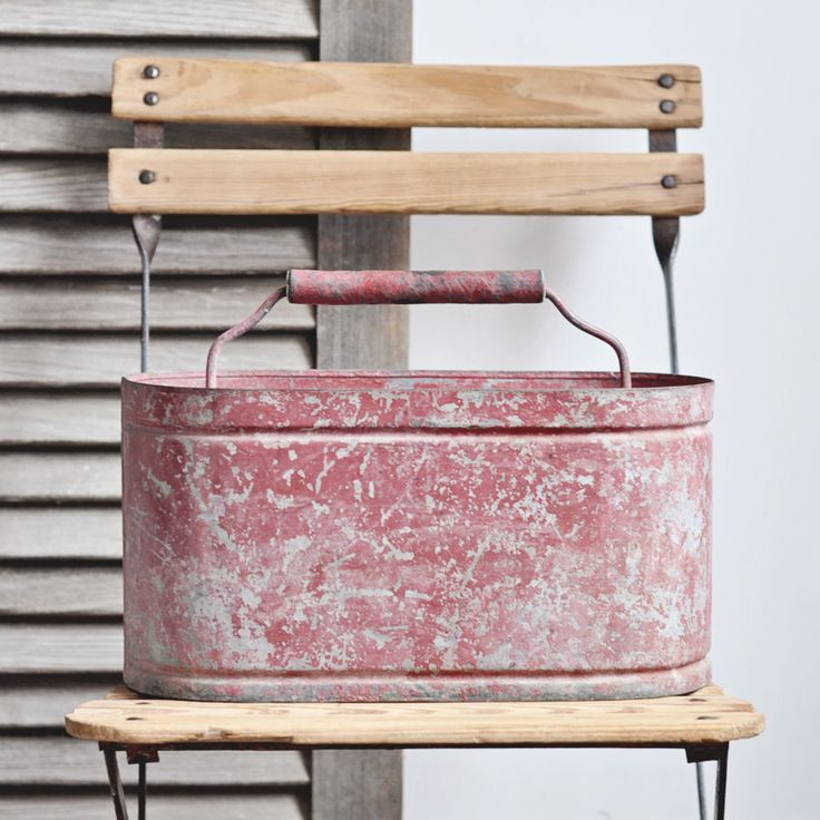 A vintage zinc pail with red chippy paint